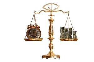 A scale measuring a clock on one end and money on the other