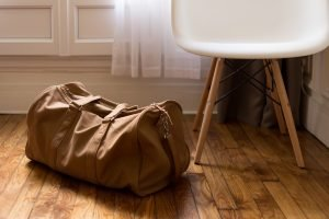 A brown traveling bag placed on a floor beside a white chair with brown legs.