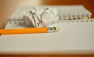 A chewed up pencil placed on a notebook. Beside it, there is a crumpled up paper ball.