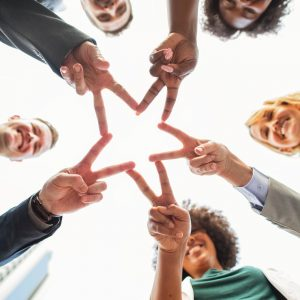 Five people holding out their hands in such a way that they shape a star with their fingers put together.