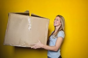A blonde woman holding a big cardboard box, and standing in front of a yellow wall.