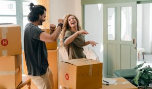 A couple in the middle of a move, surrounded by cardboard boxes.