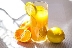 A glass of orange juice with some oranges beside it.