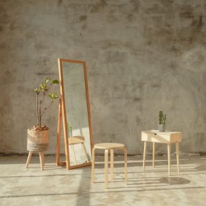 Large mirror with chairs in front of it.