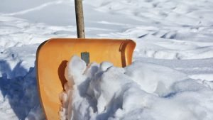 Orange shovel in snow