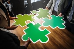 Four people holding four parts of jigsaw puzzle.