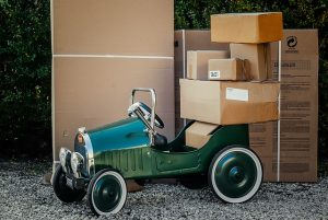Stacked cardboard boxes and a green small vehicle.