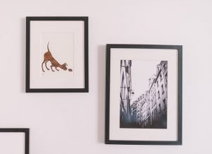 Two framed pictures on a white wall