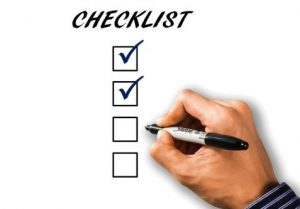 A person checking his checklist when movers are late