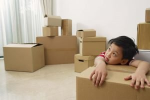 boy sitting with moving boxes