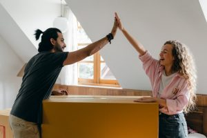A couple relocating to a new apartment giving high five
