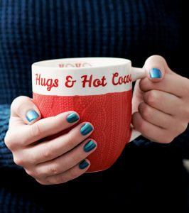 Person holding white and red mug