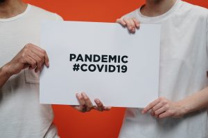 two people holding a sign about the COVID-19 pandemic