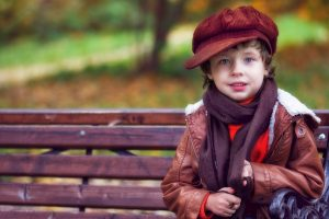 a kid sitting on a park bench
