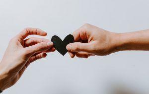 Two people sharing a paper heart