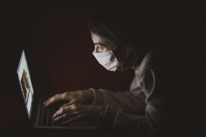 a woman wearing a face mask and typing on her laptop