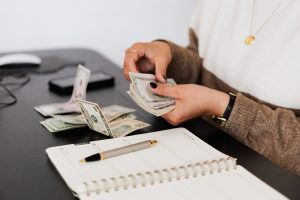 a woman sitting at a desk, counting money above a notepad