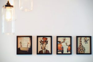a row of paintings on a white wall