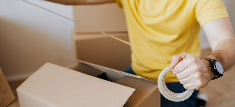 a man stretching a tape on top of a cardboard box