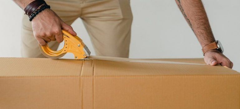 a man taping the top of a cardboard box to reinforce it as a way to pack high-value items for moving