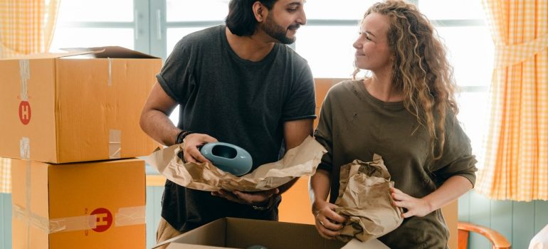 a couple smiling at each other as they pack items inside a cardboard box together