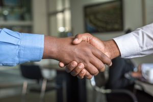 two people shaking hands in an office after finding reliable moving companies in NJ