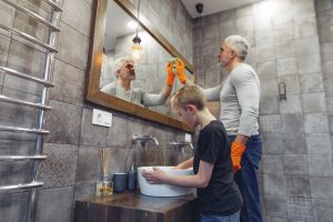 a father cleaning the bathroom with his son