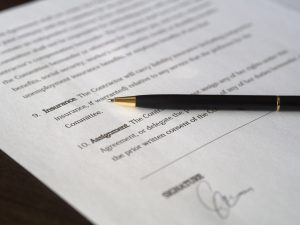 an insurance policy with a black pen on top of the paper