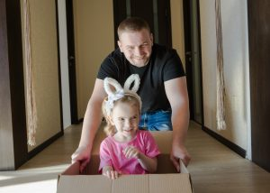 a father pushing his daughter inside a cardboard box
