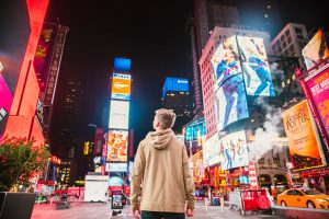 a young person standing in Times Square