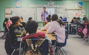 children in school listening to the professor