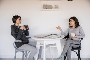 two women drinking coffee and talking at the table