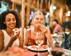 two women eating a pizza at a restaurant
